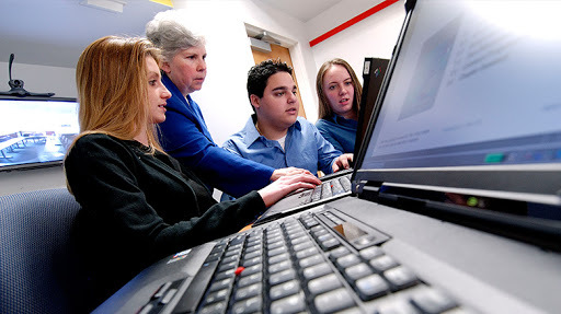 Students and a faculty member typing at computers.