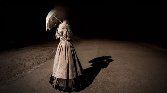 Ghostly woman holding umbrella on an ominous street.