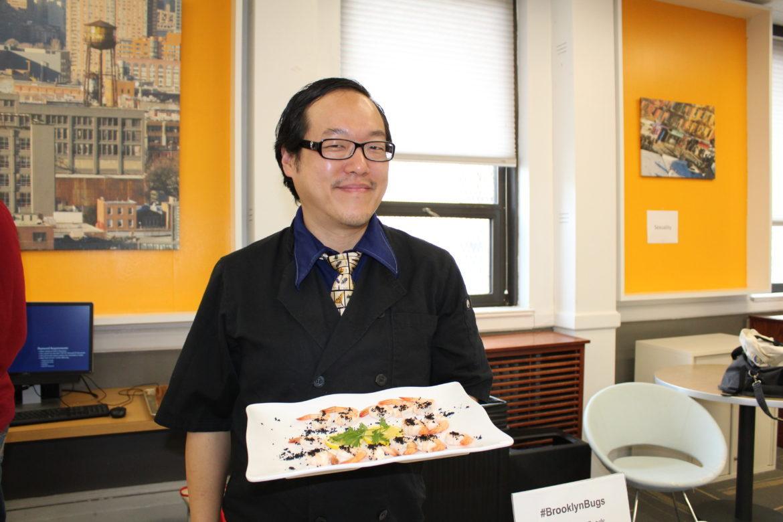 Joseph Yoon holding up his shrimp and black ants dish.
