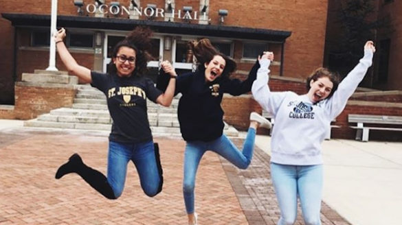Students jumping for joy at College.