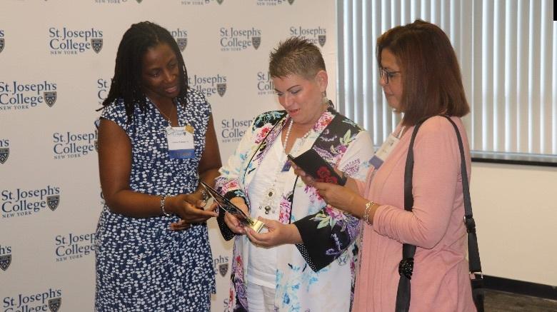 Women standing looking at award.
