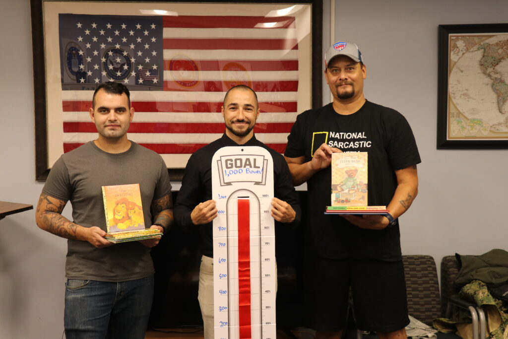 Center is John Davis holding the sign saying they reached the goal for 1,000 books, surrounded by members of SVA holding books for Cambodia.